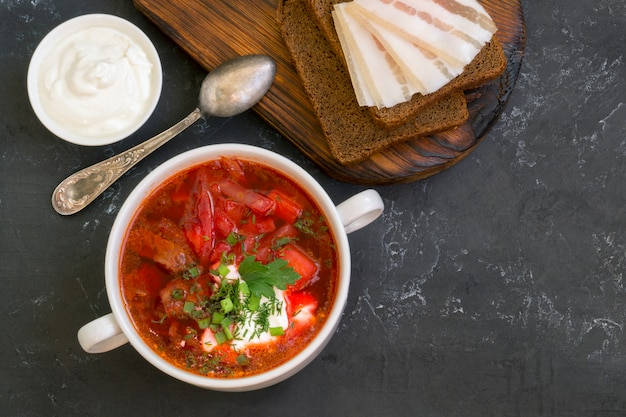 Traditional ukrainian russian soup (borscht) from beet with greens and sour cream.
