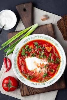 伝統的なウクライナのロシアの伝統的なビートの赤いスープ。石の背景にサワークリームとボルシチ。