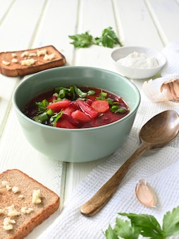 Traditional ukrainian russian vegetable soup, borsch with garlic donuts and bread.