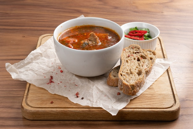 Traditional ukrainian soup made from beets, vegetables and meat with bread on a wooden table.
