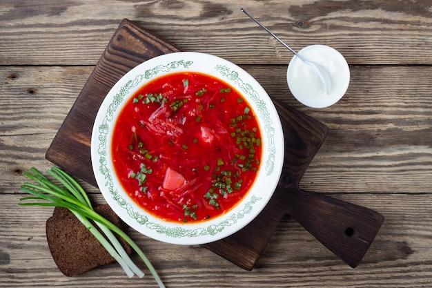 Традиционный украинский вегетарианский красный суп из свеклы - борщ со сметаной на деревянных фоне.