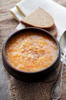 Традиционный украинский зимний суп с квашеной капустой, пшеном и мясом в деревенской миске