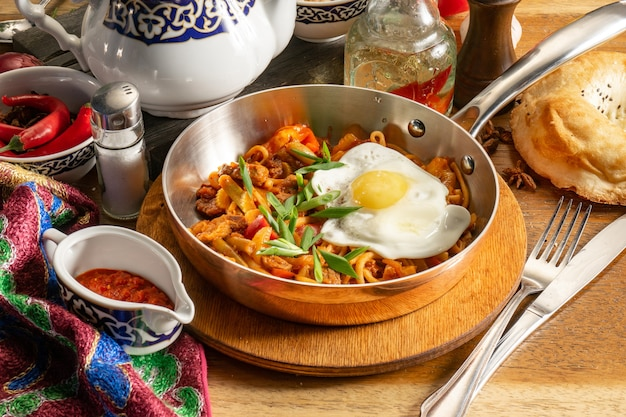 伝統的なウズベキスタンの温かい料理揚げラグマン。子羊、野菜、卵、アジカの焼きそば。