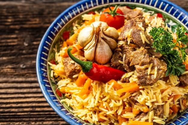 ピラフと呼ばれる伝統的なウズベク料理。オリエンタルオーナメントを添えたプレートに肉、ニンジン、タマネギを添えたライス、ウズベキスタンのオリエンタル料理。上面図。