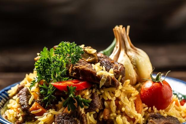 Традиционное узбекское блюдо - плов. рис с мясом, морковью и луком в тарелке с восточным орнаментом, восточная узбекская кухня.