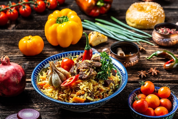 Traditional uzbek meal called pilaf. rice with meat, carrot and onion in plate with oriental ornament, uzbek oriental cuisine. long banner format. space for text.