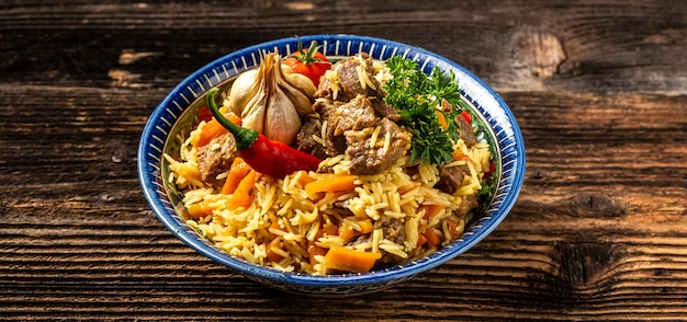 Traditional uzbek meal called pilaf. rice with meat, carrot and onion in plate with oriental ornament, wooden background, concept of oriental uzbek cuisine.
