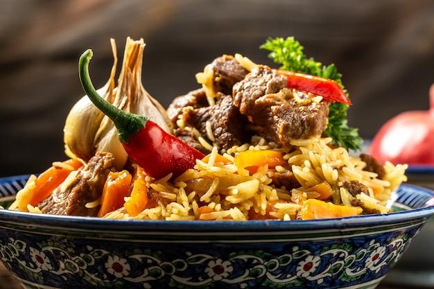 ピラフと呼ばれる伝統的なウズベク料理。暗い木製の背景に東洋の装飾が施されたプレートに肉とご飯、長いバナー形式。テキスト用のスペース。