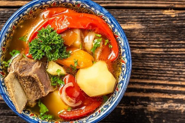 Традиционное узбекское блюдо суп шурпа с говядиной и овощами в тарелке с восточным орнаментом