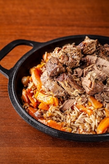 Traditional uzbek oriental cuisine, pilaf or plov with large pieces of lamb meat and carrots, cooked in a black cast-iron skillet of kazan.