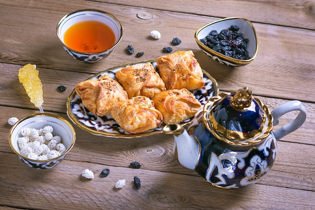 Traditional uzbek sweets - dried apricot, rohat turkish delight, raisin, samsa, almond, teapot and bowl