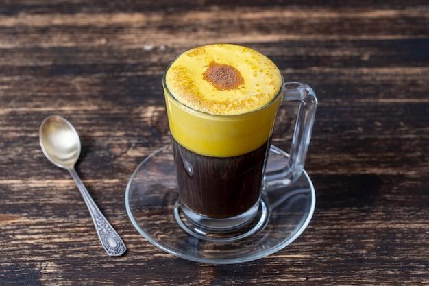 날 달걀 노른자와 농축 우유로 만든 전통적인 베트남 달걀 커피가 닫힙니다. 나무 테이블 배경에 eggcoffee