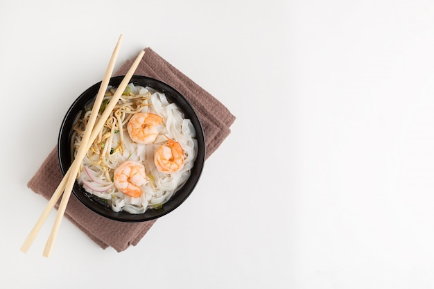 Traditional vietnamese noodle soup pho with shrimps in black bowl