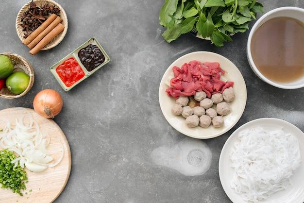 ボウル、コンクリートの背景に伝統的なベトナムのヌードルスープフォー。ベトナムビーフスープフォーボー、クローズアップ。アジア/ベトナム料理。ベトナムディナー。フォーボーミール。上面図。元気