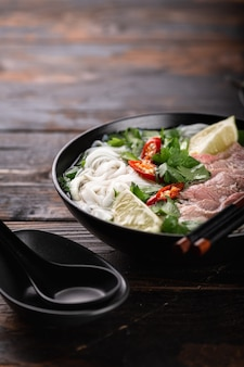 Traditional vietnamese soup pho bo with beef and noodles on a wooden surface, selective focus