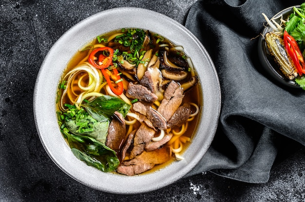Traditional vietnamese soup pho bo with herbs, meat, rice noodles, broth. black background. top view