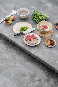 ハーブ、肉、ビーフン、スープを使った伝統的なベトナムのスープフォーボー。箸、スプーンでボウルにフォーボー。テキスト用のスペース。上面図。木製のテーブルの背景にアジアのスープフォーボー。ベトナムのスープ