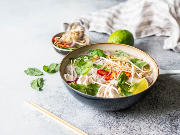 Traditional vietnamese soup- pho ga in bowl with chicken and rice noodles