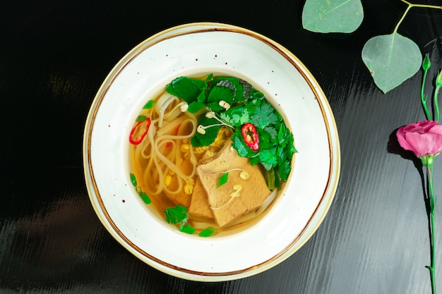 Traditional vietnamese and tasty pho bo - noodle soup with mint, beef and hot pepper in white bowl on dark