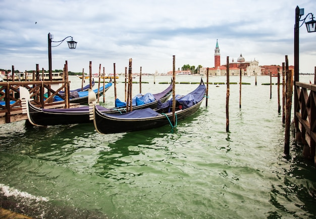Traditional view from san marco, venice, italy. blue gondolas parked on canal grande, san giorgio maggiore church at the background