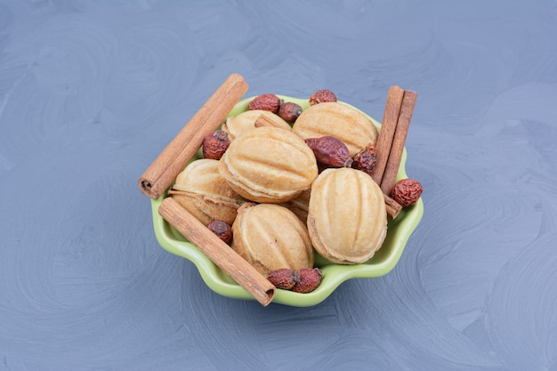 Traditional walnut cookies with cinnamon sticks and dry hips in a green cup