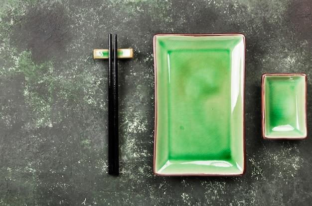 Традиционная посуда для азиатской кухни на зеленом фоне. вид сверху, скопируйте пространство. пищевой фон