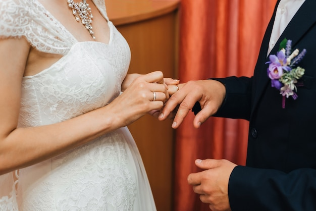 Traditional wedding ceremony of exchange of gold rings between the bride and groom