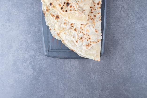 Pane di lavash di grano tradizionale sul vassoio di legno sul tavolo di marmo.