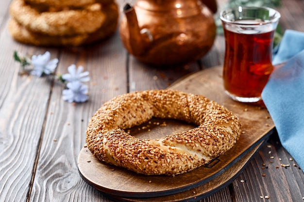 Traditional white bread with sesame seeds for breakfast, a glass of armudu with red tea on a wooden table