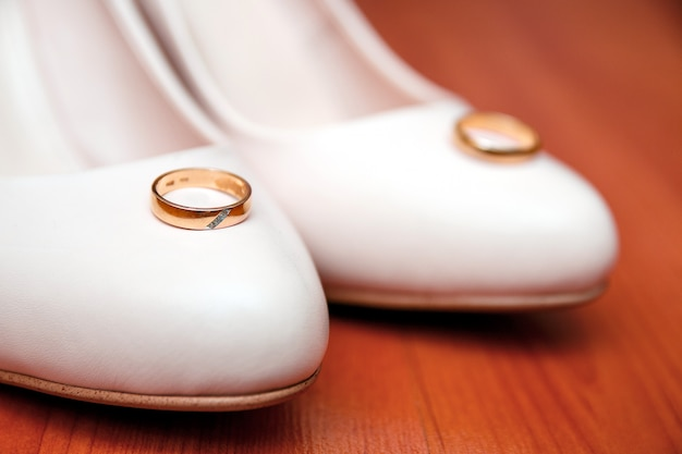 Traditional white wedding shoes with rings on wooden .