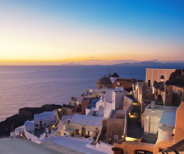 Traditional windmill and apartments in oia village, santorini, greece