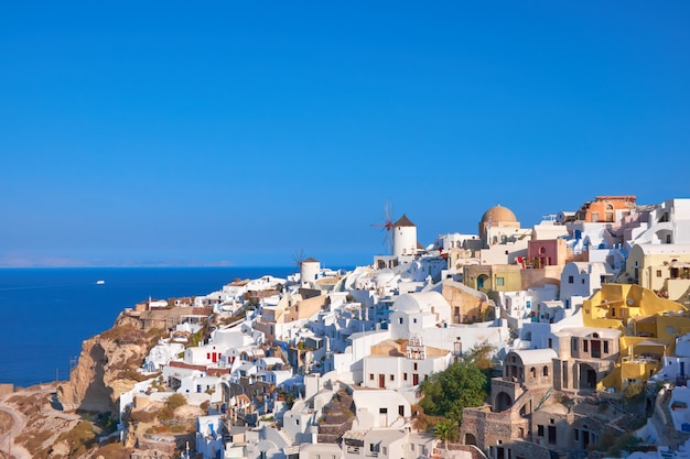 Traditional windmill and apartments in oia village in santorini