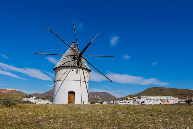 Traditional windmill and behind the village of el pozo de los frailes, windmill traditional in spain, pozo de los frailes, province of almeria, windmill under blue sky
