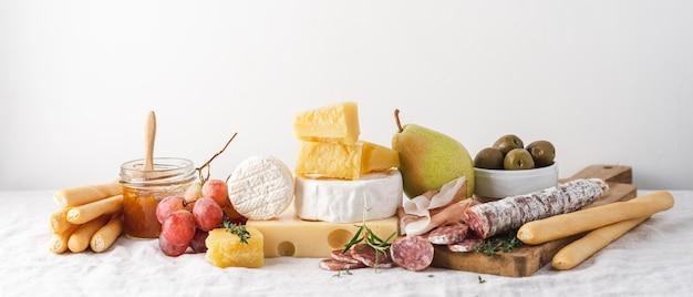 Традиционные винные закуски на столе, покрытом скатертью. сыр, колбаса, ветчина, фрукты, джем и хлебные палочки гриссини на столе