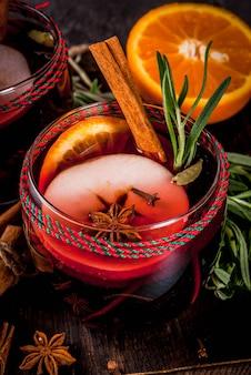 伝統的な冬と秋の飲み物。クリスマスと感謝祭のカクテル。オレンジ、リンゴ、ローズマリー、シナモン、暗い石の背景にスパイスとホットワイン、コピースペース平面図
