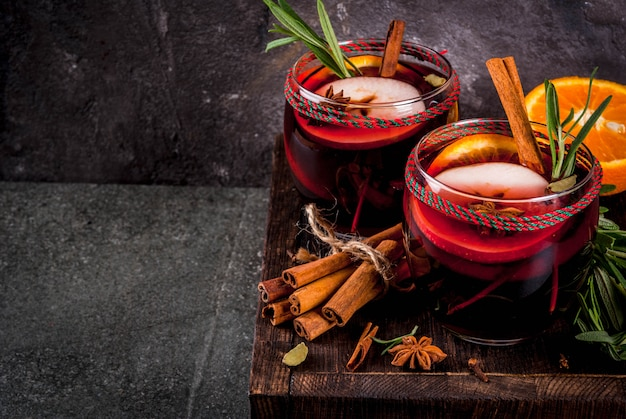 伝統的な冬と秋の飲み物。クリスマスと感謝祭のカクテル。オレンジ、リンゴ、ローズマリー、シナモン、暗い石背景の上面にスパイスとホットワイン