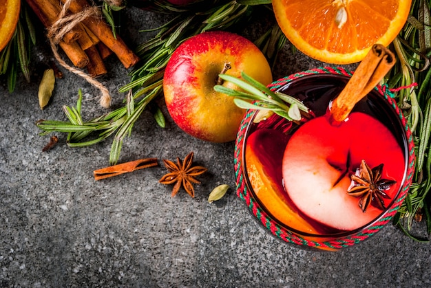 伝統的な冬と秋の飲み物。クリスマスと感謝祭のカクテル。オレンジ、リンゴ、ローズマリーとホットワイン、