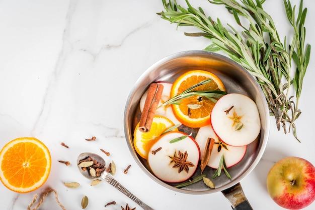 伝統的な冬とクリスマスの飲み物、柑橘類、リンゴ、白い大理石のテーブルの上のアルミのキャセロールのスパイスとホットワインの材料。コピースペーストップビュー