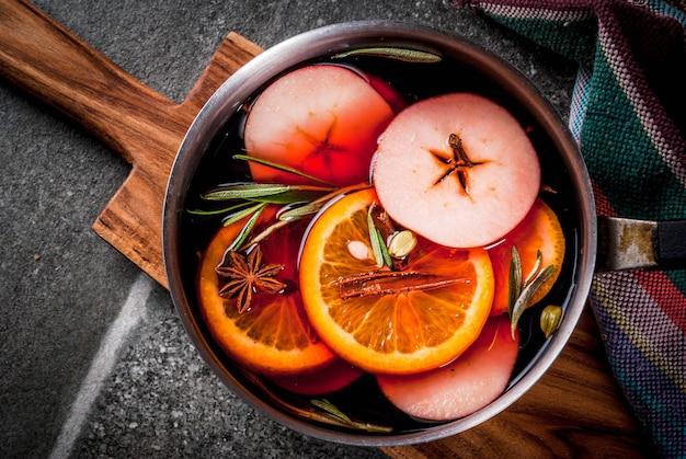 伝統的な冬とクリスマスの飲み物、柑橘類、リンゴ、黒い石のテーブルの上のアルミキャセロールのスパイスとホットワイン。コピースペーストップビュー