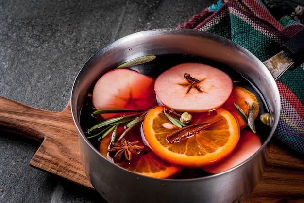 伝統的な冬とクリスマスの飲み物、柑橘類、リンゴ、黒い石のテーブルの上のアルミキャセロールのスパイスとホットワイン。コピースペース