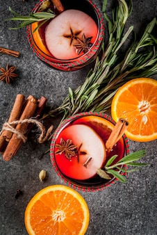 Traditional winter and autumn drinks. christmas and thanksgiving cocktails. mulled wine with orange, apple, rosemar