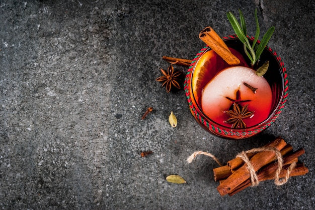 Traditional winter and autumn drinks. christmas and thanksgiving cocktails. mulled wine with orange, apple, rosemary, cinnamon and spices on a dark stone , copyspace top view