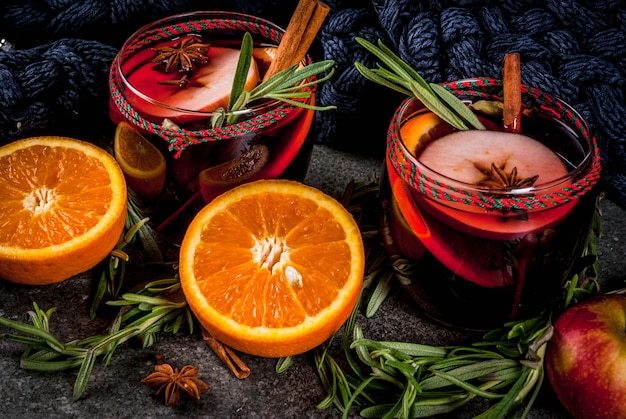 Traditional winter and autumn drinks. christmas and thanksgiving cocktails. mulled wine with orange, apple, rosemary, cinnamon and spices on a dark stone , copyspace