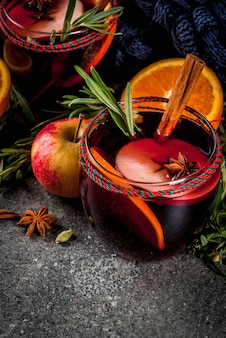 Traditional winter and autumn drinks. christmas and thanksgiving cocktails. mulled wine with orange, apple, rosemary, cinnamon and spices on a dark stone ,
