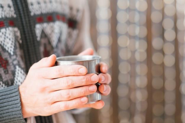 伝統的な冬の飲み物。鋼のマグカップで温かい飲み物を持って、手を温める男のクロップドショット。