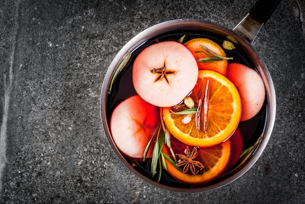 Traditional winter and christmas beverage, mulled wine hot drink with citrus, apple and spices in aluminum casserole on black stone table. copy space top view