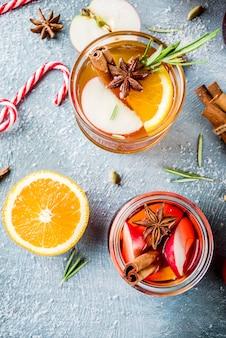 伝統的な冬の飲み物、白と赤のホットワインカクテル、白と赤のワイン、スパイス、リンゴ、オレンジ。水色のテーブルの上に、