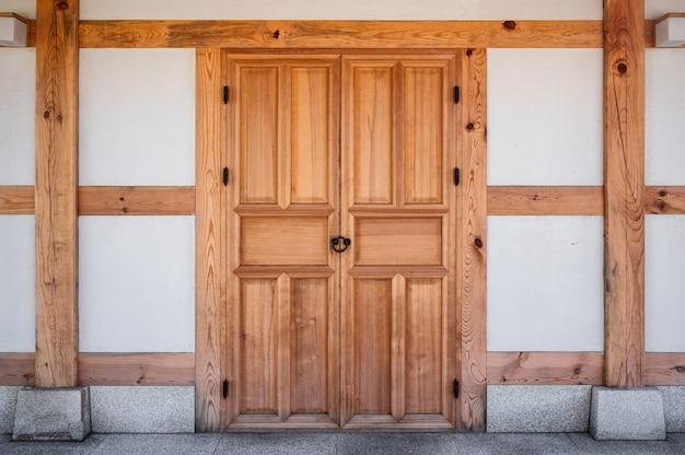Традиционная деревянная коричневая закрытая двустворчатая дверь в восточном стиле