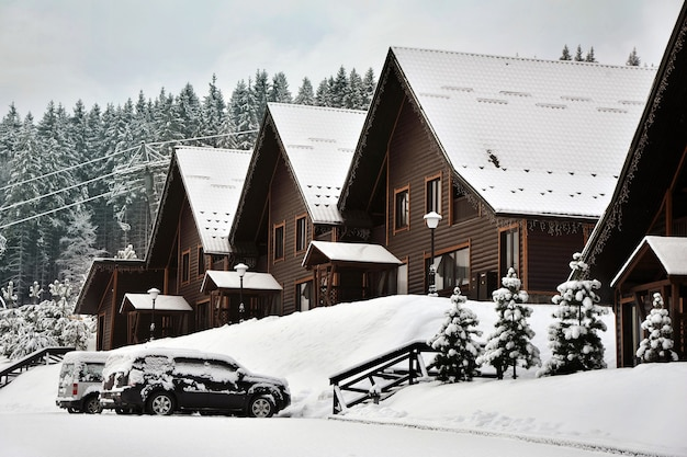 Traditional wooden houses on a hill slope in the mountains of carpathians surrounded by snow-capped fir trees.