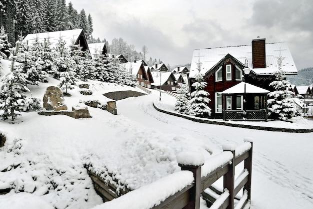 눈 덮힌 전나무로 둘러싸인 carpathians 산의 언덕 경사면에 전통적인 목조 주택.